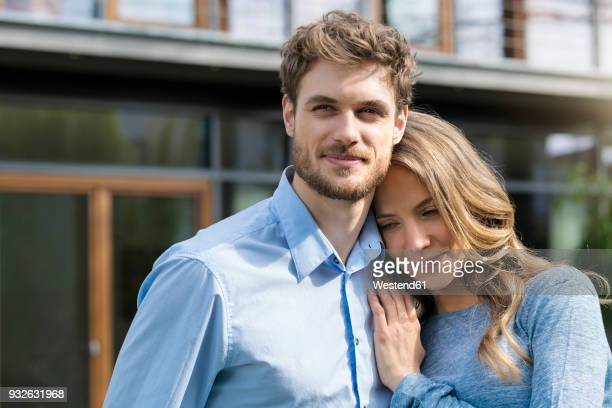 portrait of smiling affectionate couple in front of their home - heterosexual couple stock pictures, royalty-free photos & images