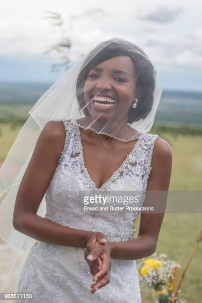 portrait of smiling african american bride with veil over face - wedding veil stock photos and pictures