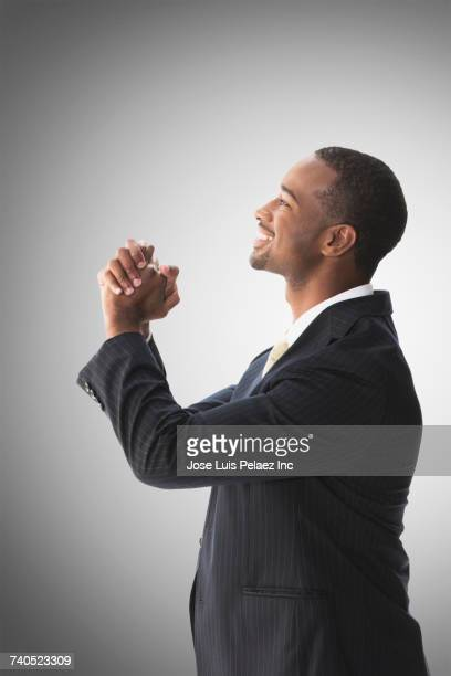 Portrait of smiling African American businessman with hands clasped