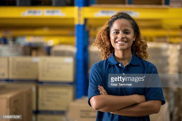 portrait of smiling african female warehouse manager with arms crossed in distribution warehouse center.  supply chain, warehouse management. - polo foto e immagini stock