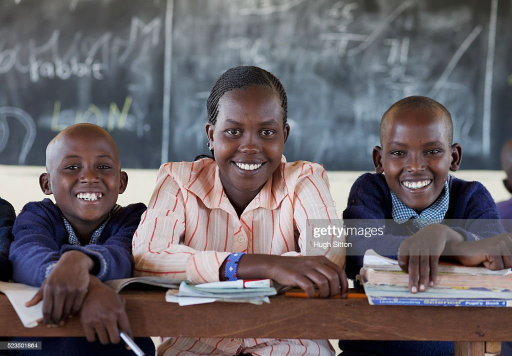 Portrait of smiling African schoolboys (10-12) with teacher in classroom : Stock Photo