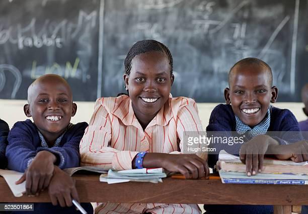 portrait of smiling african schoolboys (10-12) with teacher in classroom - hugh sitton stockfoto's en -beelden