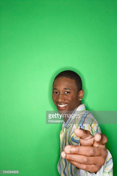 Portrait of smiling African-American teen boy holding hand out toward viewer against green background.