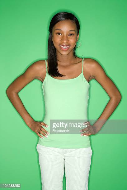 Portrait of smiling African-American teen girl with hands on hips standing against green background.