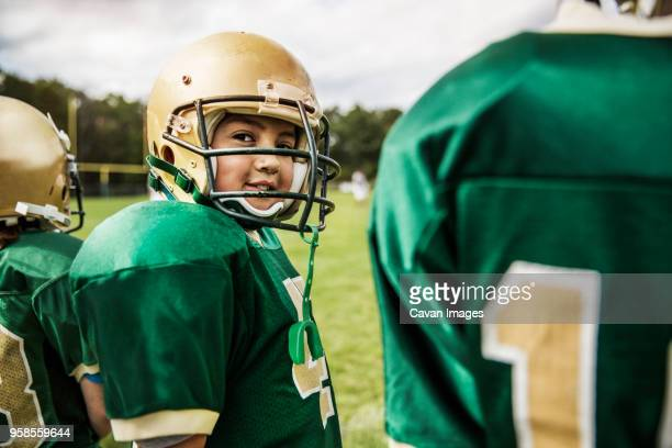 portrait of smiling american football player with friends on field - american football team stock pictures, royalty-free photos & images