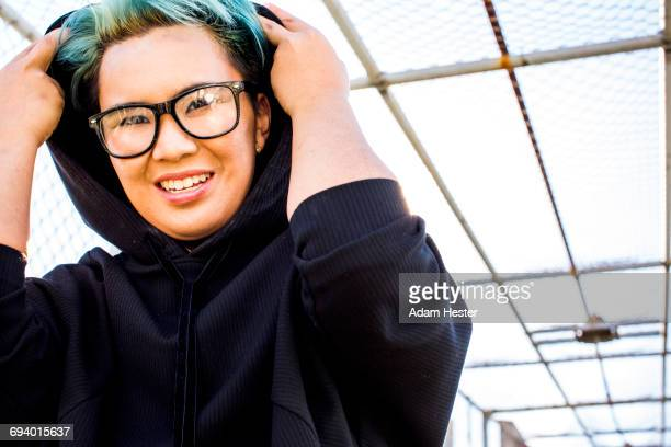 portrait of smiling androgynous asian woman wearing hoodie - non binary gender stock pictures, royalty-free photos & images
