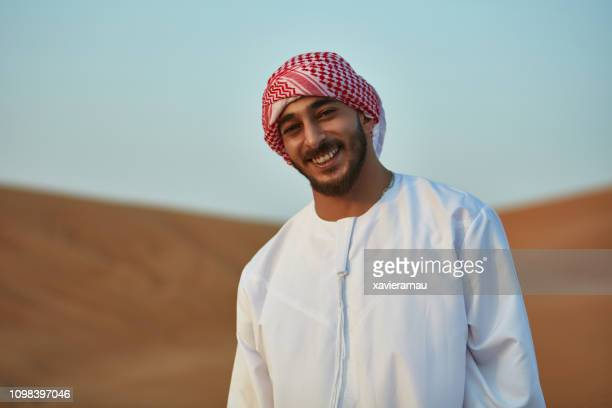 portrait of smiling arab man standing in desert - kaffiyeh stock pictures, royalty-free photos & images