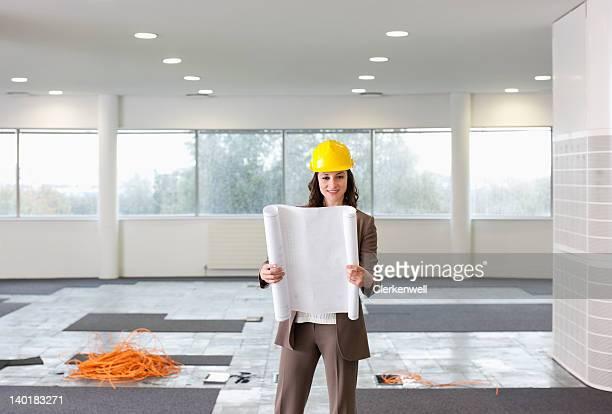 Porträt von lächelnd Architekt holding Blaupausen in leere Büro