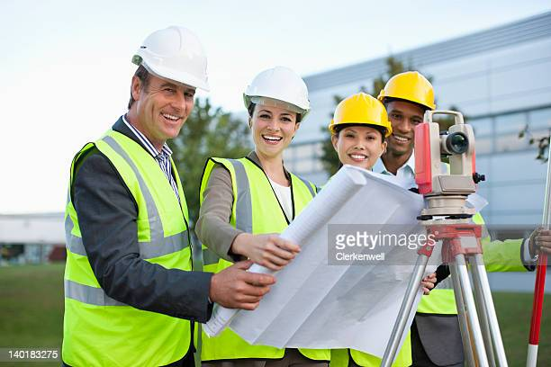 Portrait of smiling architects with blueprint and theodolite