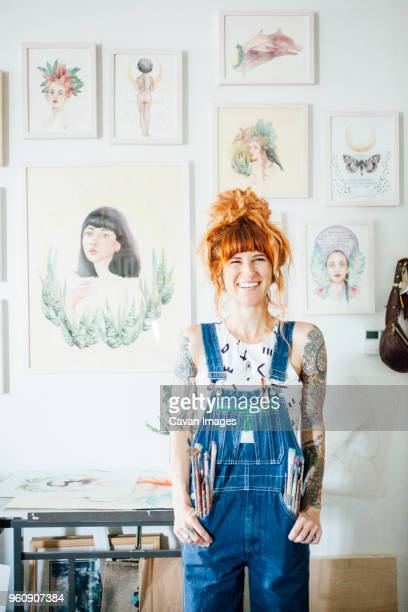 portrait of smiling artist with hands in pockets standing in studio - painter artist stock pictures, royalty-free photos & images