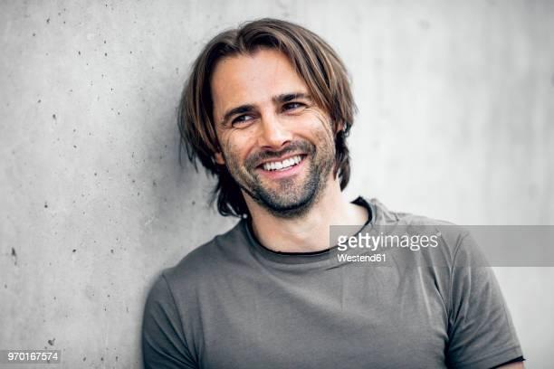 portrait of smiling athlete at concrete wall - barba por fazer imagens e fotografias de stock