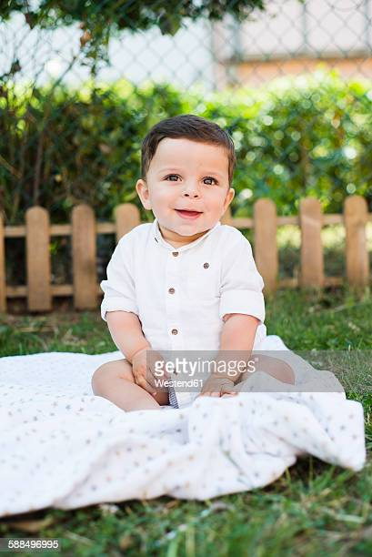 Portrait of smiling baby boy sitting on a blanket in the garden