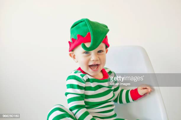 Portrait of smiling baby boy sitting on chair against white background