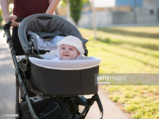 portrait of smiling baby girl in pram - baby stroller stock pictures, royalty-free photos & images