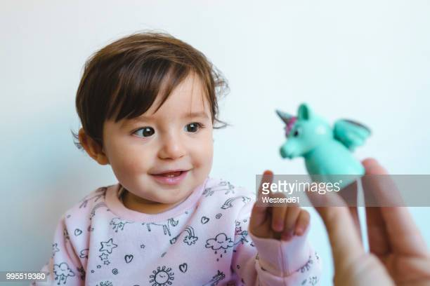 portrait of smiling baby girl looking at unicorn figure - baby pointing stock photos and pictures