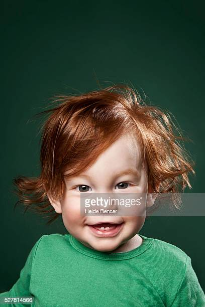 portrait of smiling baby girl (12-23 months) with red hair - black ginger baby stock photos and pictures
