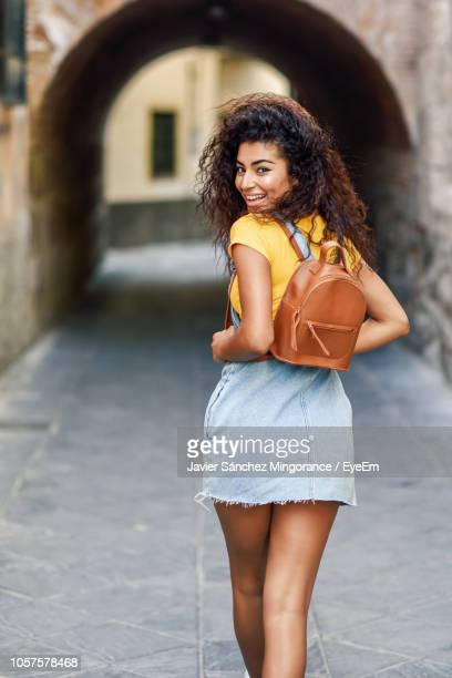 Portrait Of Smiling Backpack Young Woman Standing On Street