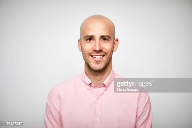 portrait of smiling bald businessman in pink shirt - frontaal stockfoto's en -beelden