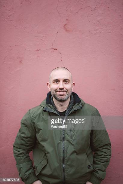 Portrait of smiling bald man standing in front of a wall