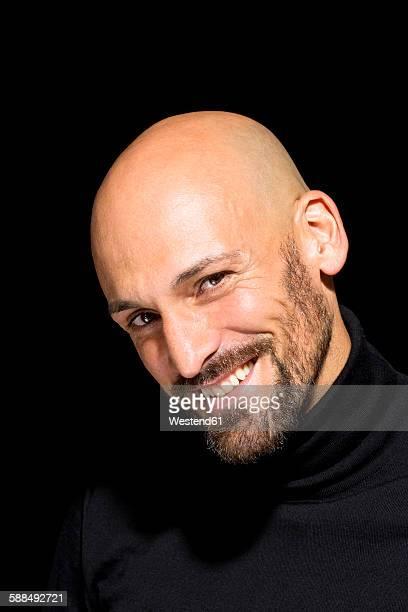 portrait of smiling bald man with wearing black turtleneck in front of black background - col roulé photos et images de collection
