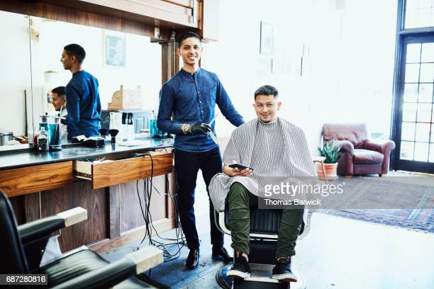 portrait of smiling barber and customer in barber shop - 美容室 椅子 ストックフォトと画像