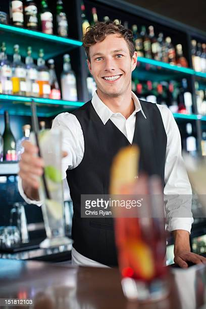 Porträt eines lächelnden Barkeeper holding cocktail