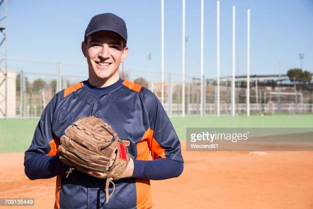 Portrait of smiling baseball player with a baseball glove