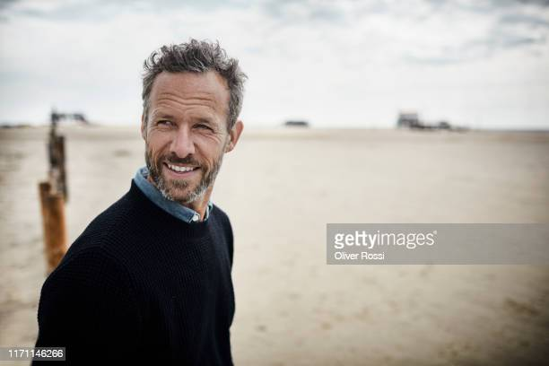 portrait of smiling bearded man on the beach - mature men stock pictures, royalty-free photos & images
