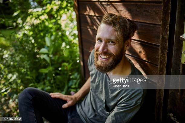 portrait of smiling bearded man resting at garden shed - zufriedenheit stock-fotos und bilder