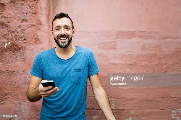 Portrait of smiling bearded man with smartphone