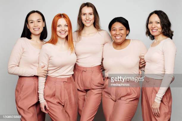 portrait of smiling beautiful real women embracing each other against isolated background, international womens day concept - international womens day stock pictures, royalty-free photos & images