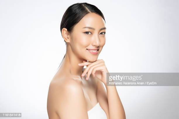portrait of smiling beautiful woman against white background - hand on chin stock pictures, royalty-free photos & images