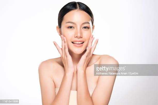 portrait of smiling beautiful woman against white background - 人の肌 ストックフォトと画像