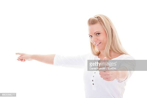 Portrait Of Smiling Beautiful Woman Gesturing While Pointing Against White Background