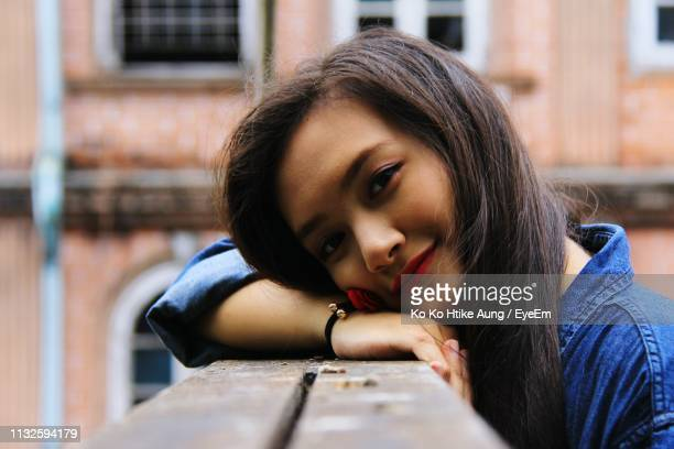 portrait of smiling beautiful woman leaning on railing against building - ko ko htike aung stock pictures, royalty-free photos & images