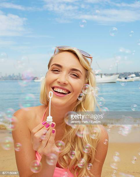 Portrait Of Smiling Beautiful Woman Playing With Bubbles At Beach