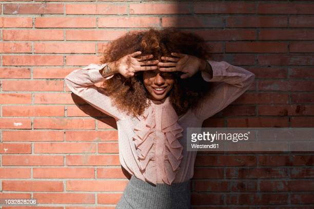 portrait of smiling beautiful young woman with afro hairdoat brick wall in sunshine - frizzy stock pictures, royalty-free photos & images