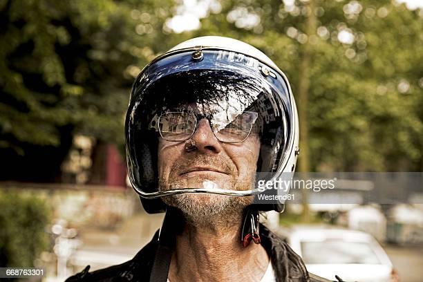 portrait of smiling biker looking through vizor of his motorcycle helmet - crash helmet stock pictures, royalty-free photos & images