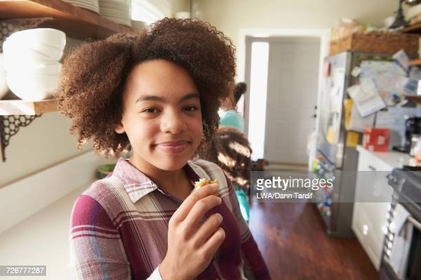 Portrait of smiling Black girl eating food in domestic kitchen