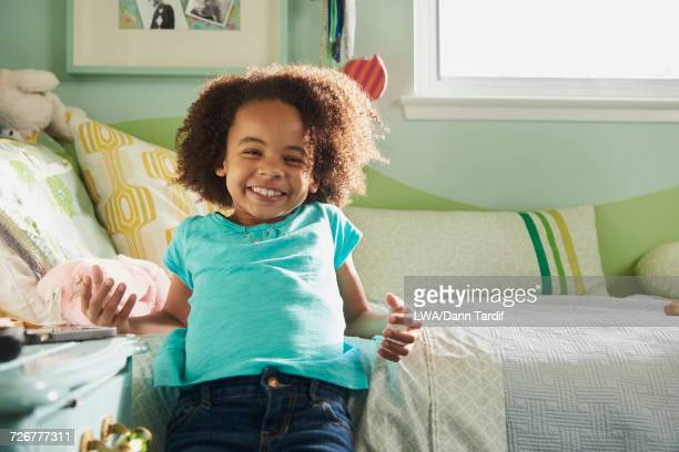 Portrait of smiling Black girl laying on bed