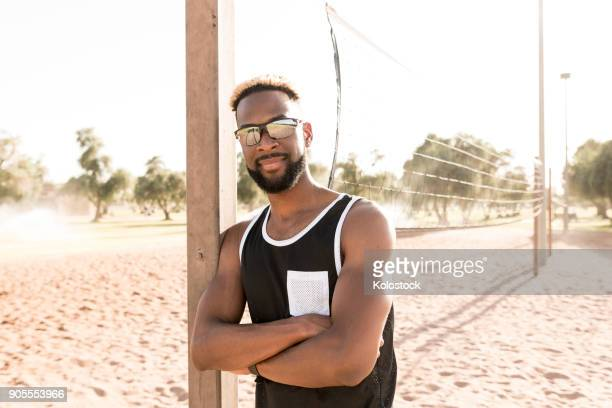 portrait of smiling black man leaning on beach volleyball net - strand volleyball der männer stock-fotos und bilder
