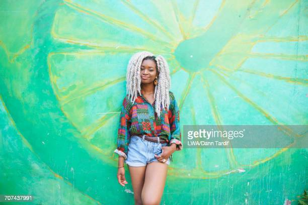 Portrait of smiling Black woman leaning on wall