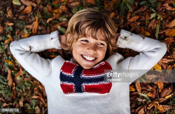 Portrait of smiling blond boy wearing pullover with Norwegian Flag