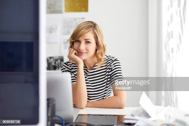 Portrait of smiling blond business woman with laptop