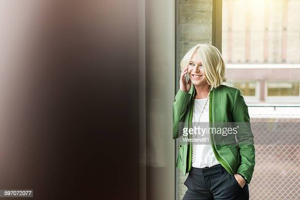Portrait of smiling blond businesswoman telephoning with smartphone