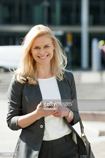 portrait of smiling blond businesswoman with cell phone and handbag - une seule femme d'âge moyen photos et images de collection