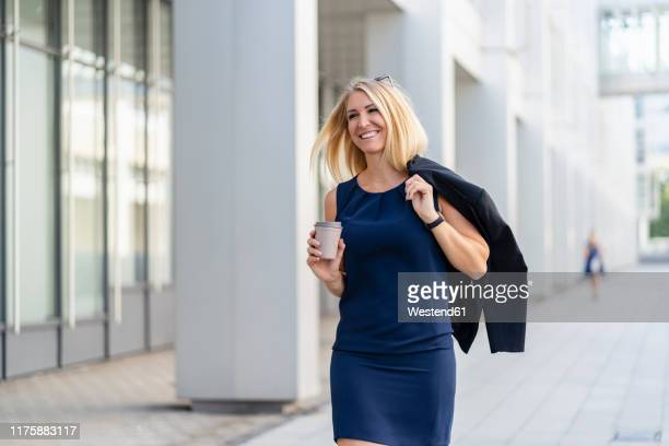 portrait of smiling blond businesswoman with coffee to go wearing blue summer dress - blue blazer stock pictures, royalty-free photos & images