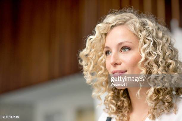 portrait of smiling blond businesswoman with ringlets - gelockt stock-fotos und bilder