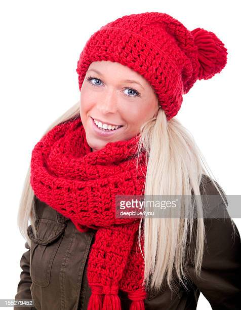 Portrait of smiling blond female with blue eyes wearing a red knitted beanie and scarf and a brown coat in front of white background