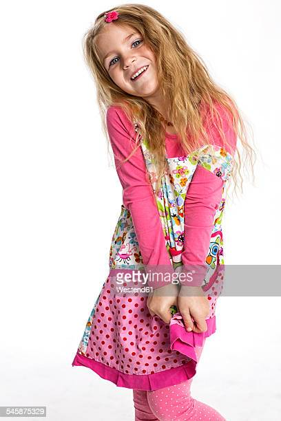 Portrait of smiling blond girl wearing colourful dress in front of white background